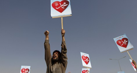 Afghan protester shouts while holding a sign during a peaceful demonstration in Kabul