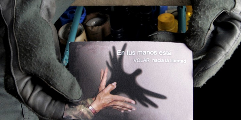 A policeman holds a leaflet which were thrown from a helicopter in the sector of Colombian forest near Abejorral