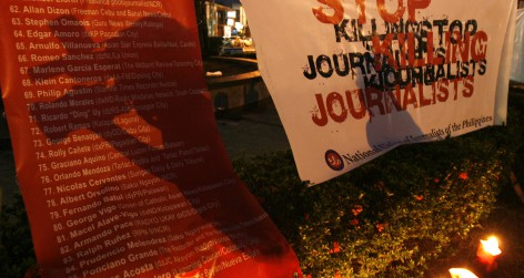 A cameraman's shadow is reflected on a poster of names of journalists who were slain in Philippines, during a prayer rally in commemoration of World Press Freedom Day in Manila