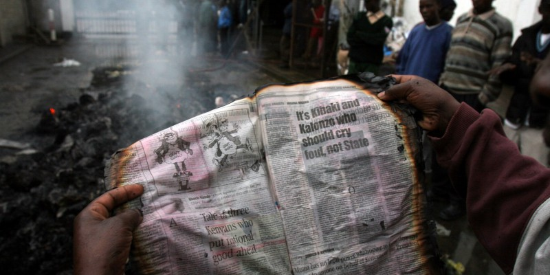 A Kenyan reads a burnt copy of the Standard newspaper at the printing press in the Kenyan capital Nairobi