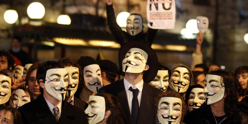 Demonstrators wearing Fawkes masks protest against Spain's Culture Minister Gonzalez-Sinde in Madrid
